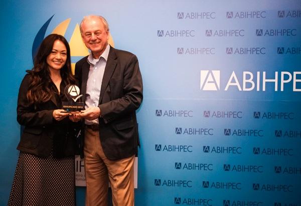 Sra Elisa Vocci recebendo a estatueta de Fornecedor Qualificado pelas mãos do presidente da ABIHPEC, o Sr. João Carlos Basílio.