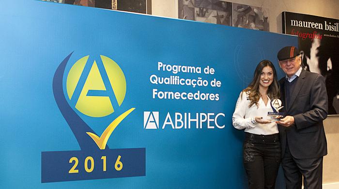 Amanda Omodei, recebe a estatueta de Fornecedor Qualificado pelas mãos do presidente da ABIHPEC, o Sr. João Carlos Basílio.